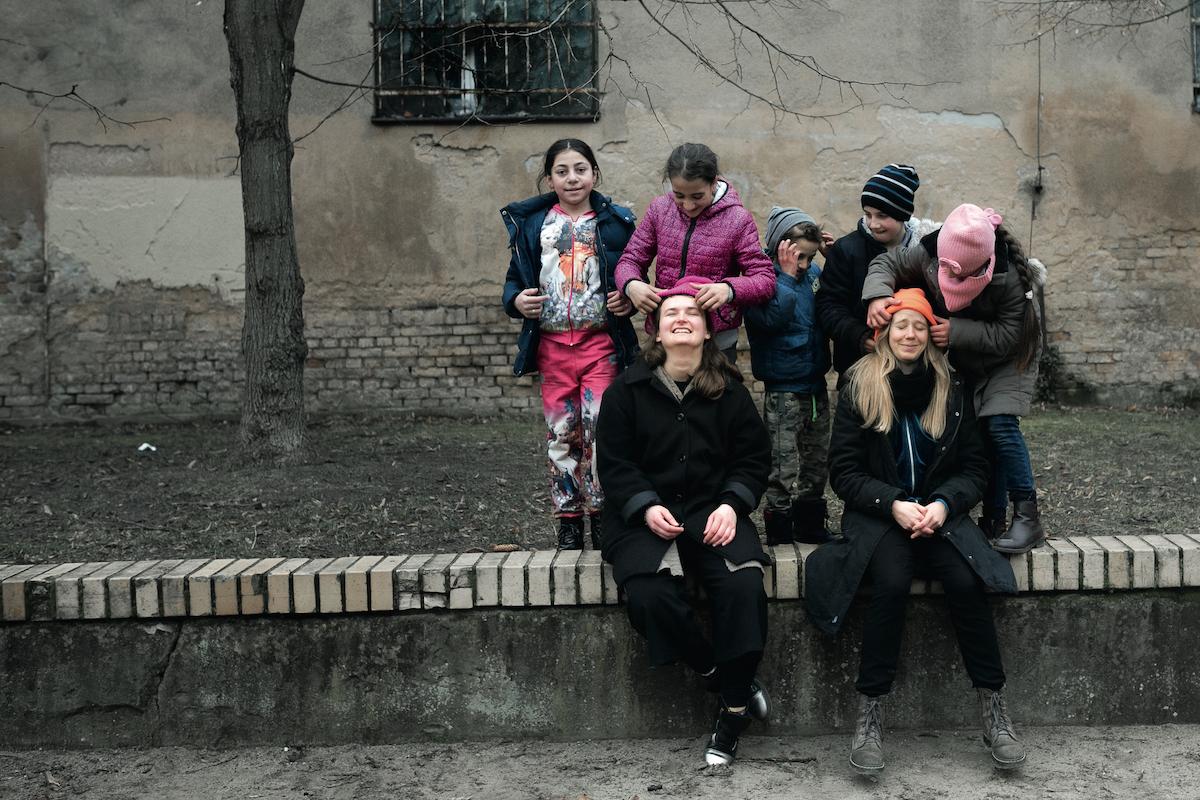 Kobiety bawią się z dziećmi na dworze, śmieją się w stronę aparatu.