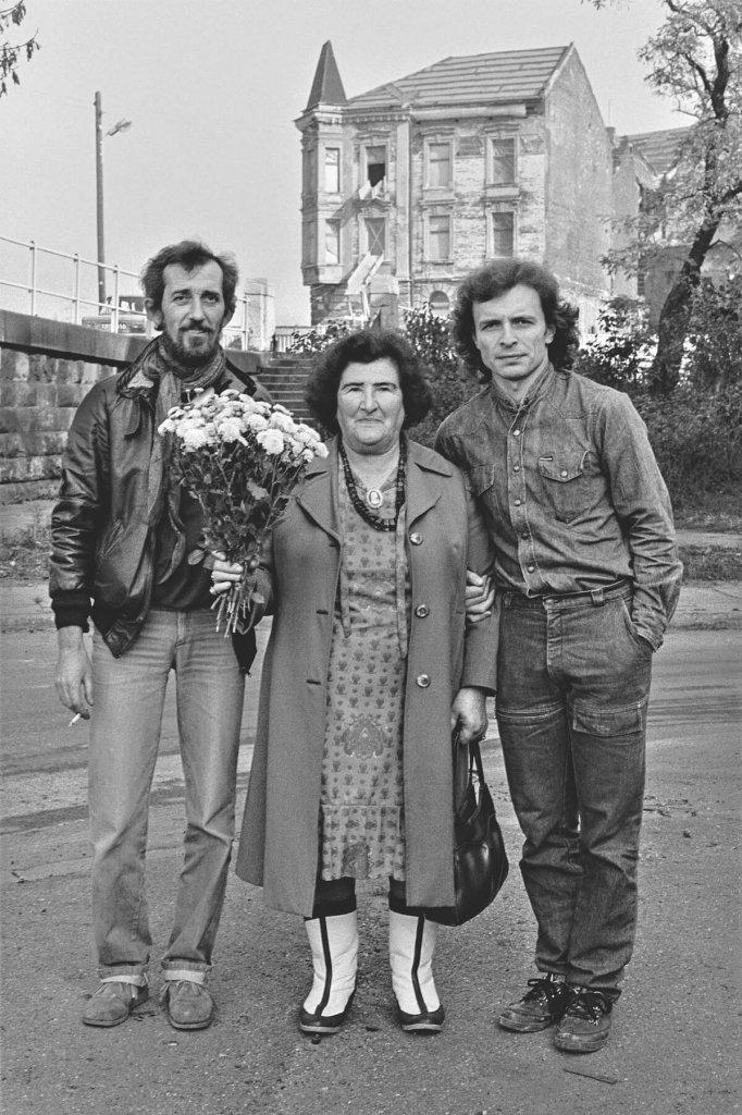 Kobieta z bukietem kwiatów w towarzystwie dwóch mężczyzn.