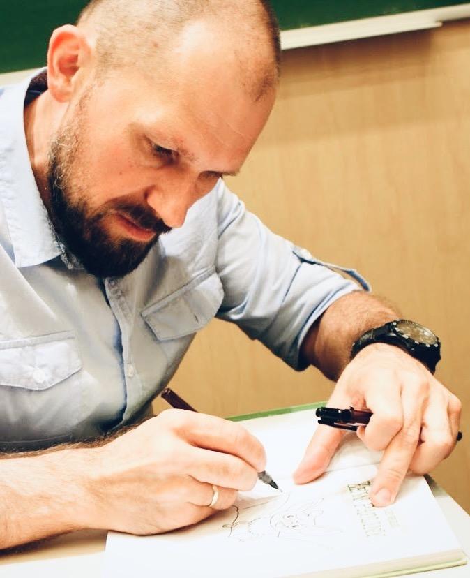 Ilustrator Tomasz Samojlik rysuje na książce dla dzieci.