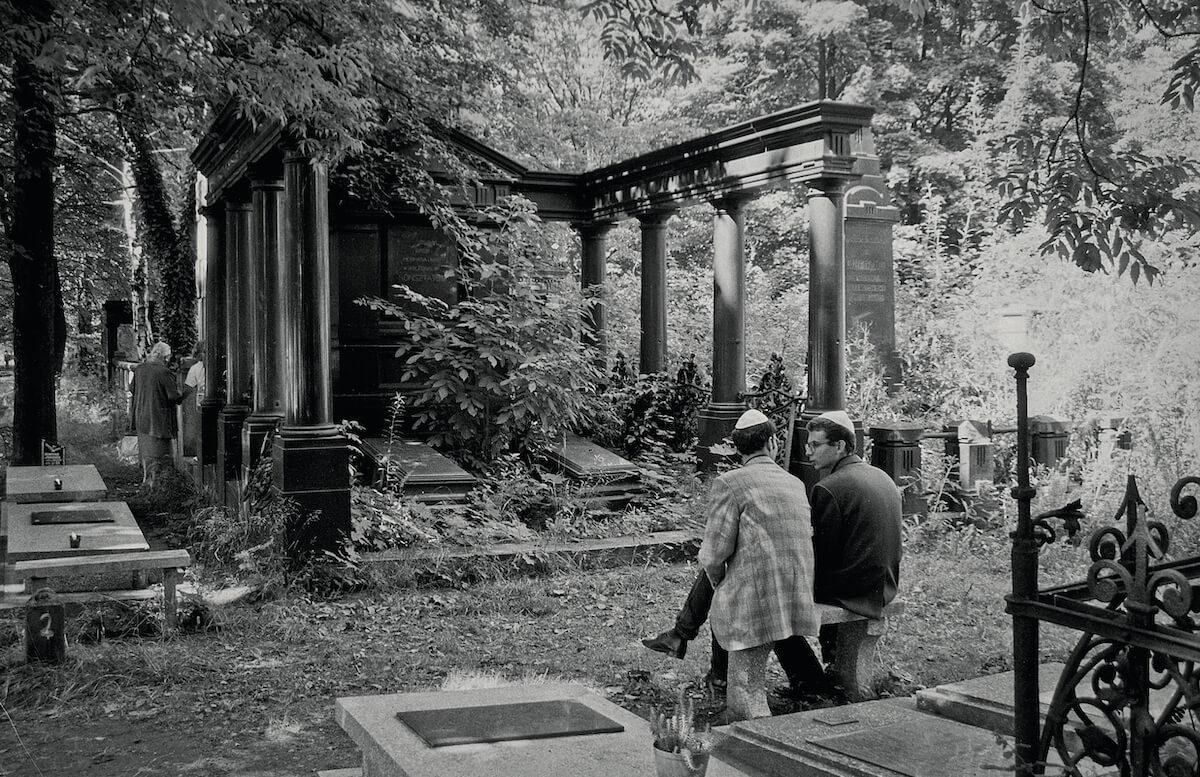 Dwójka mężczyzn rozmawia na cmentarzu żydowskim w Łodzi.