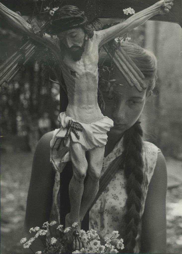 Dziewczynka z krzyżem i kwiatami.