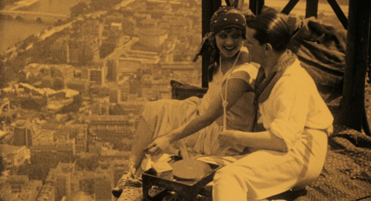 Plakat przedstawiający parę, która robi piknik na wieżowcu w budowie.
